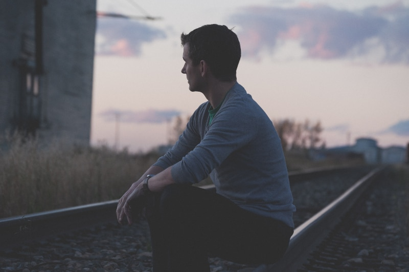 Mann sitzt auf der Eisenbahn