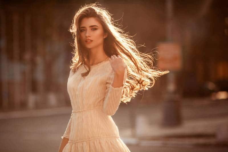 Schöne junge Dame mit langen Haaren und süßem Kleid auf der Straße