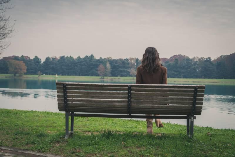Schöne junge Frau mit langen Haaren, die auf einer Bank in einem Stadtpark sitzen