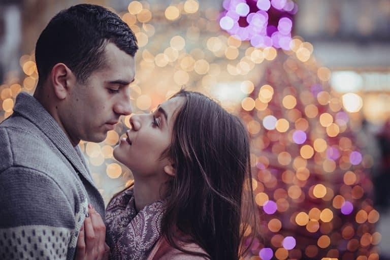 ein paar küssen vor einem weihnachtsbaum