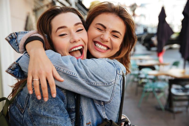 ein Bild von umarmenden und lächelnden Freunden