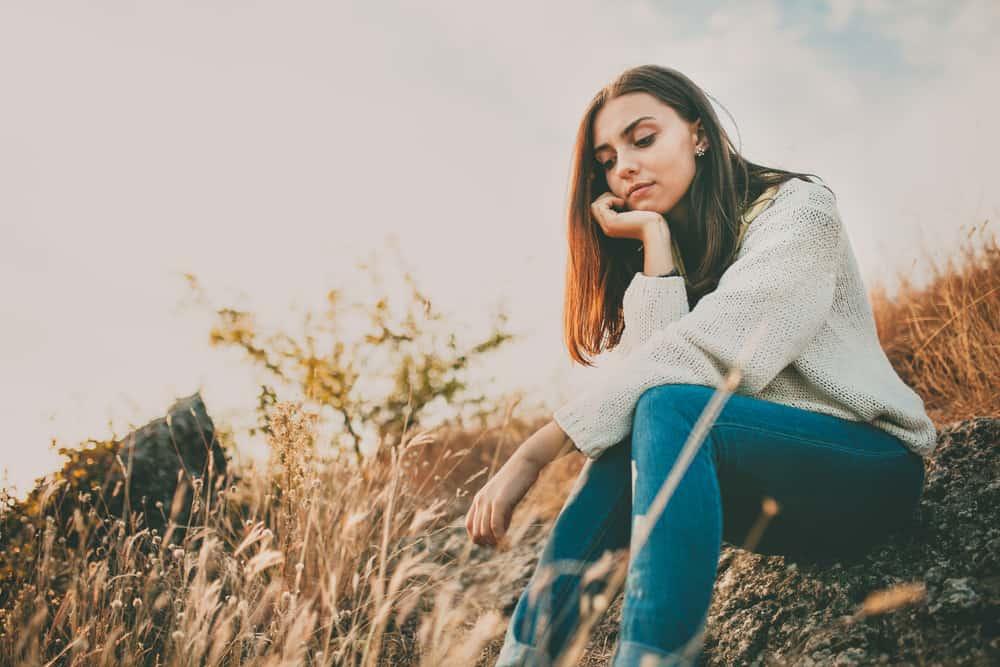 ein trauriges junges Mädchen, das alleine auf einem Felsen sitzt