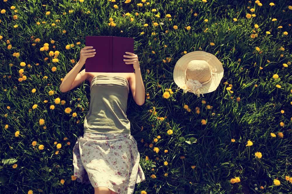 eine Frau, die im Gras liegt und ein Buch liest