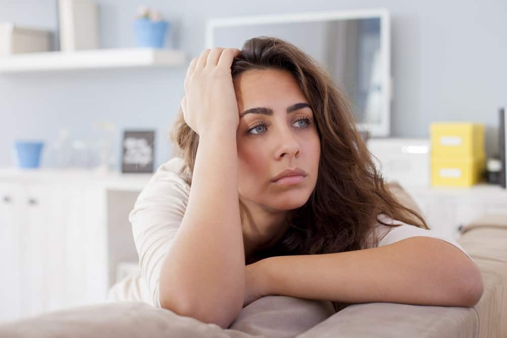 eine schöne Frau, die auf der Couch sitzt und traurig nachdenkt
