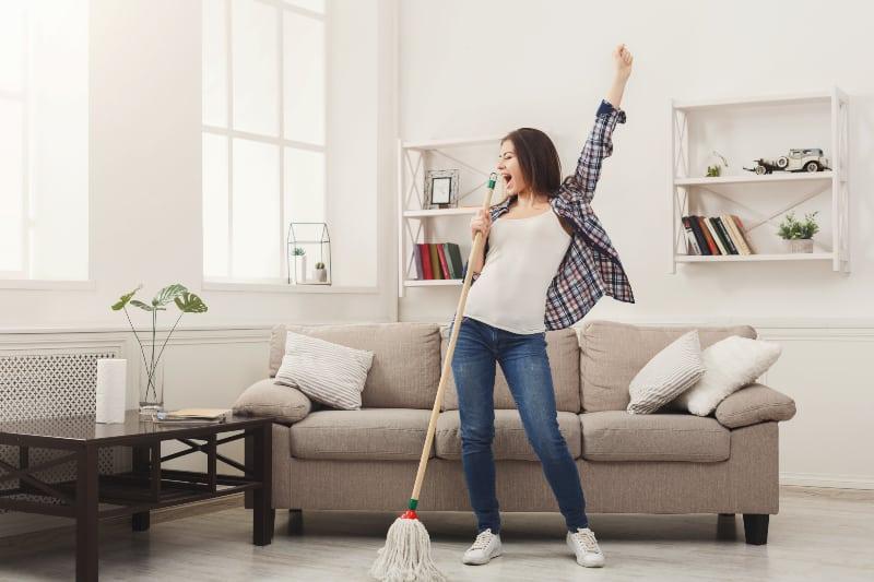 glückliche Frau putzt die Wohnung