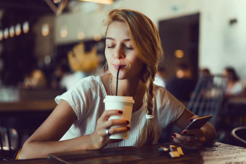 glückliches Mädchen benutzt Smartphone in der Cafeteria
