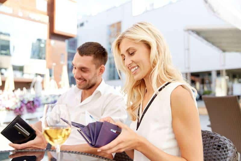 glückliches Paar mit Brieftasche und Weingläsern, die Rechnung im Restaurant bezahlen