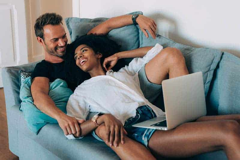 lächelndes Paar, das zusammen auf der Couch liegt