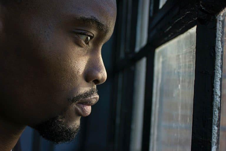 Ein schwarzer Mann schaut aus dem Fenster