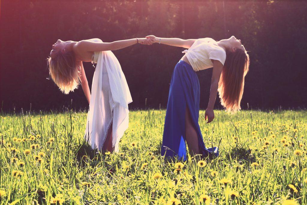 Auf der Wiese stehen zwei langhaarige Frauen, die sich an den Händen halten