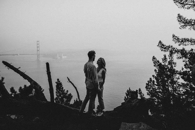 Paar, das auf dem Hügel nahe Meer steht