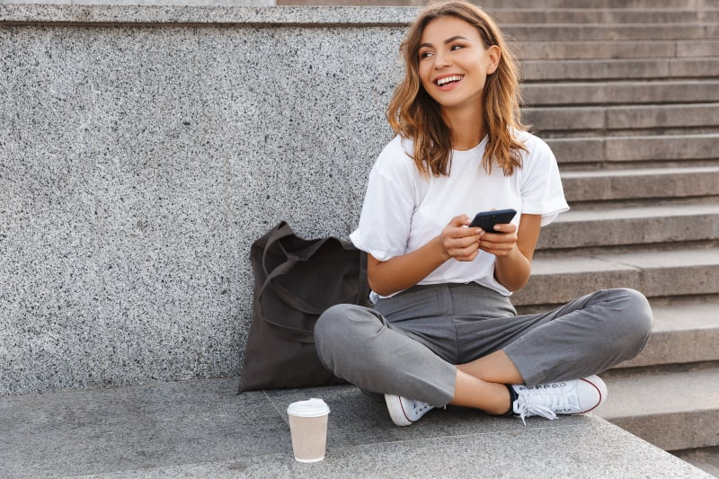 Das Mädchen sitzt auf der Treppe und hält ein Handy in den Händen