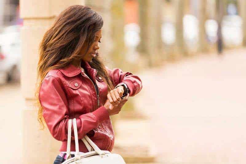 Das Mädchen in der roten Jacke schaut auf die Uhr