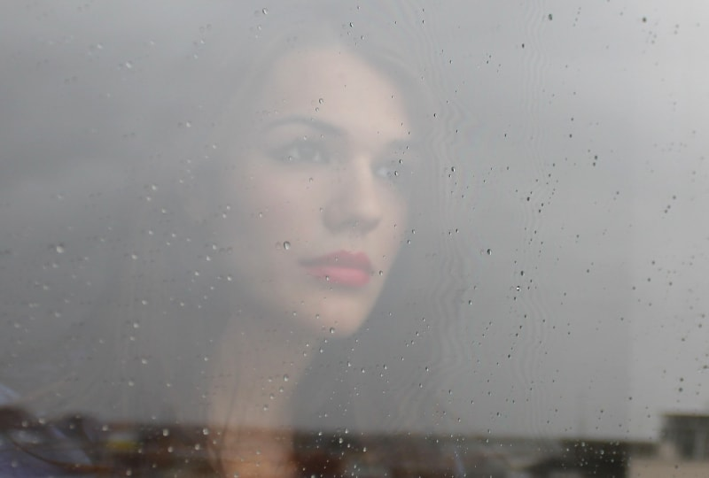 Das Mädchen schaut aus dem regennassen Fenster