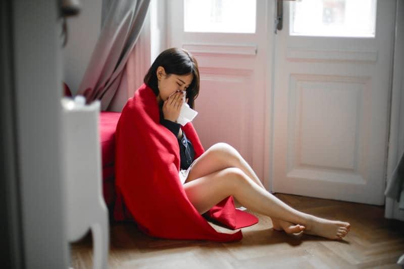 Die Frau sitzt auf dem Boden des Schlafzimmers und wischt sich mit einem Taschentuch die Nase ab