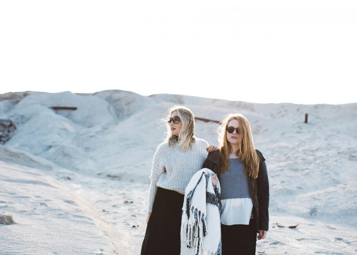 Zwei Frauen mit Sonnenbrille stehen nebeneinander