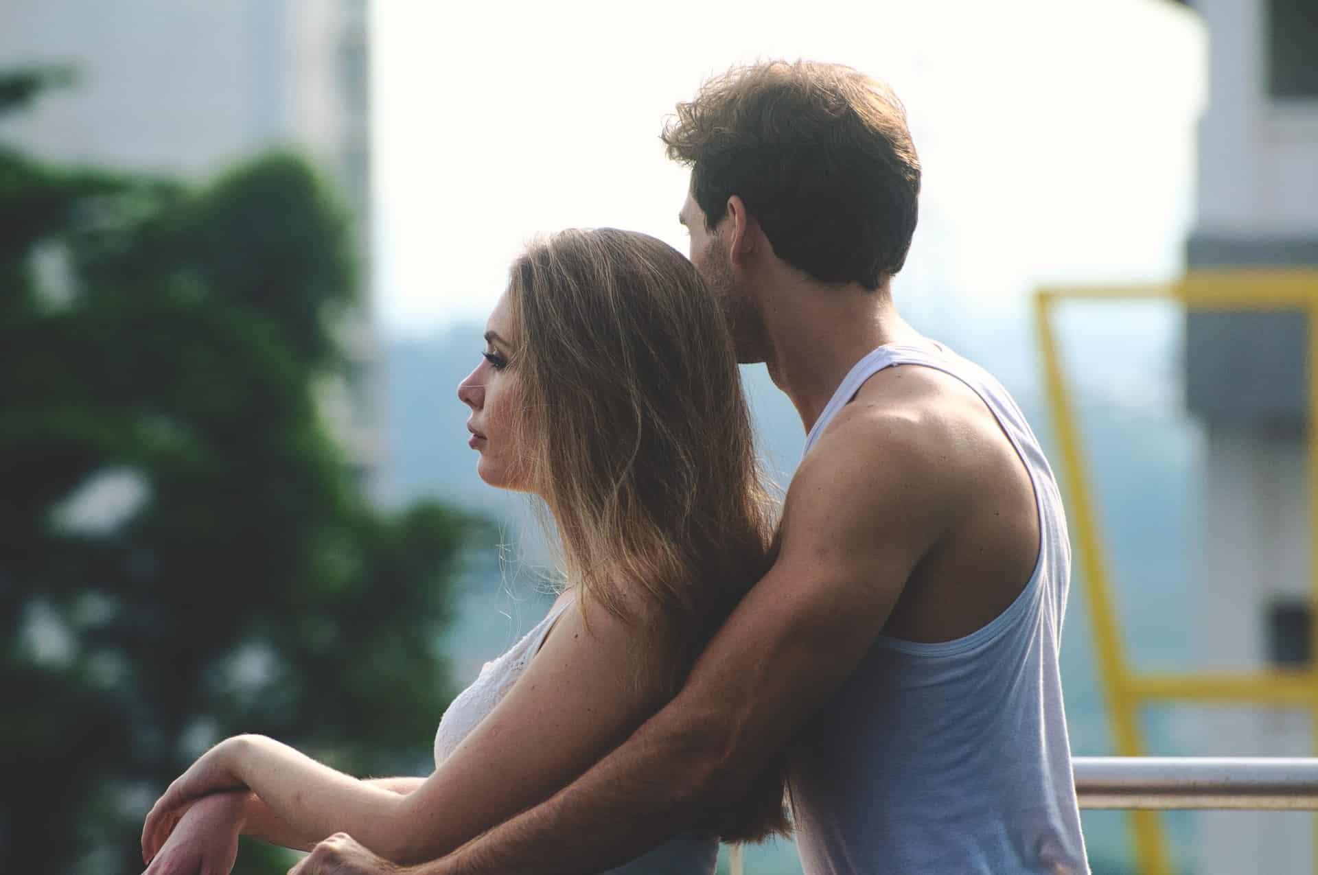 Ein Mann in einem Unterhemd umarmt eine Frau hinter seinem Rücken auf der Terrasse