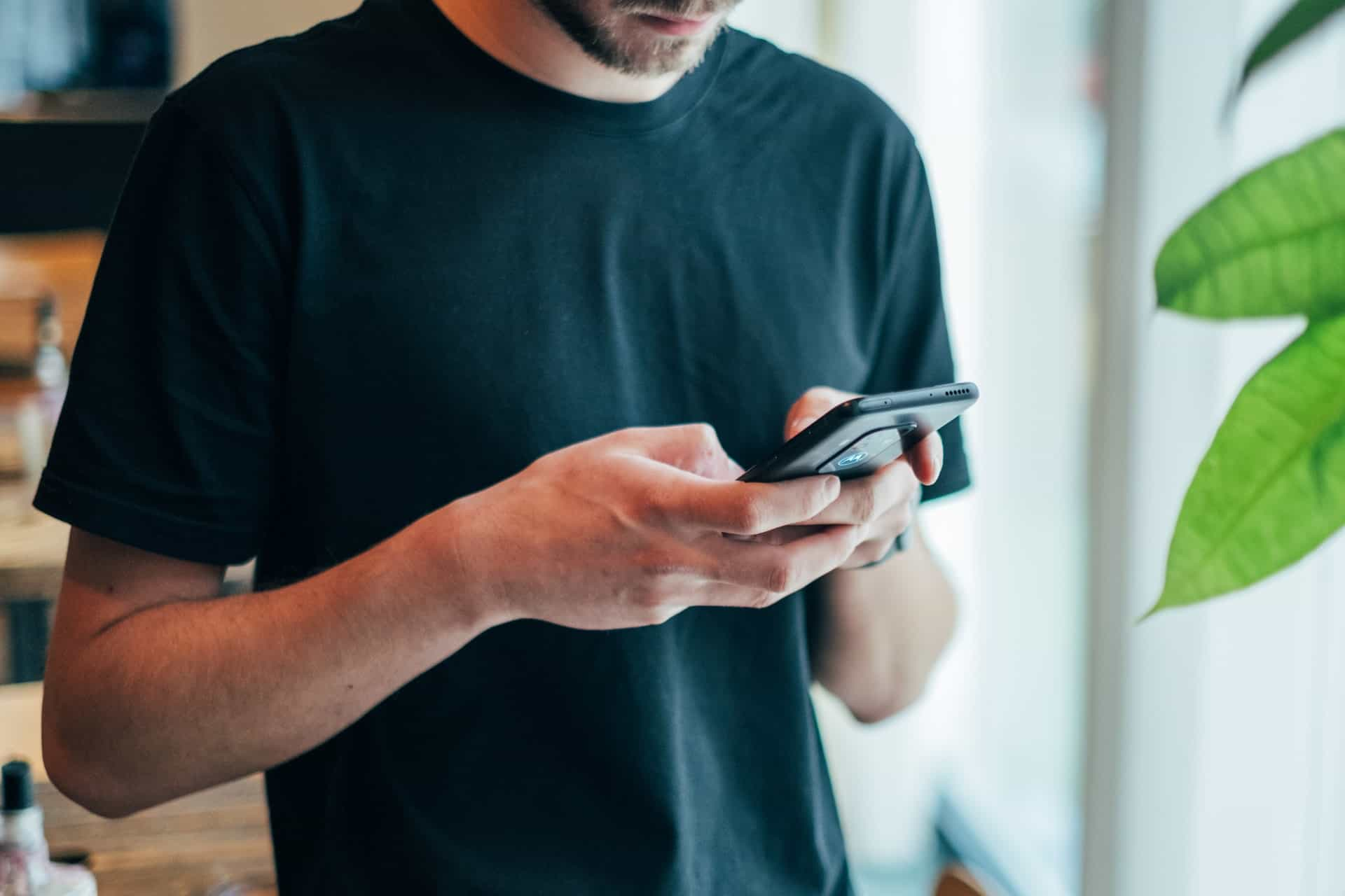 Ein Mann mit Bart im T-Shirt schreibt eine SMS
