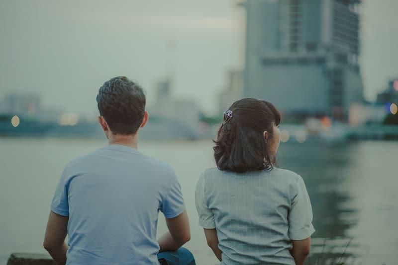 Ein liebendes Paar sitzt am Ufer eines Flusses und löst sich auf