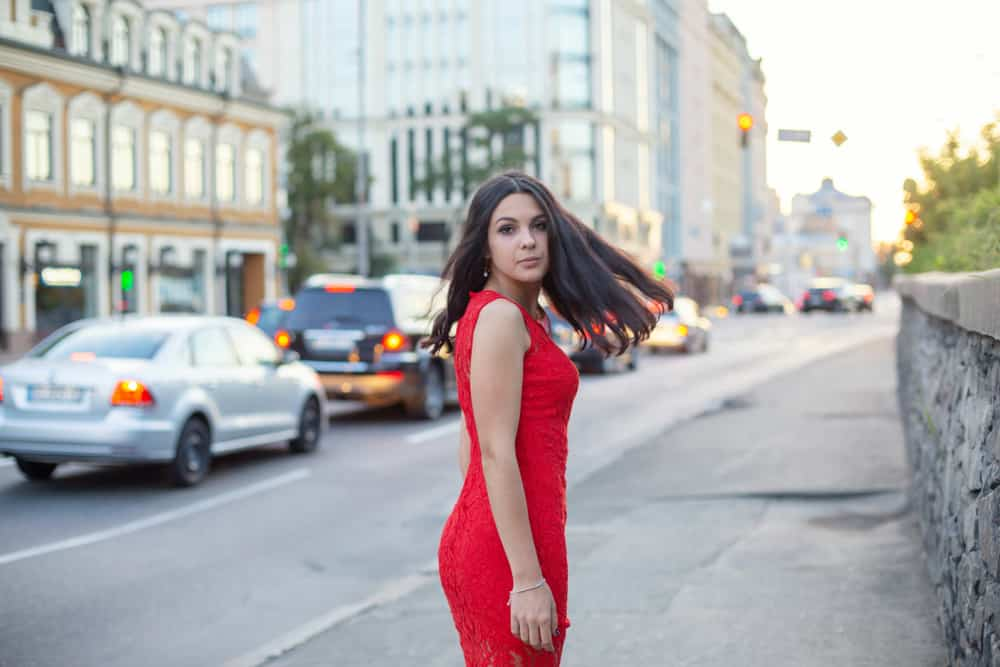 Eine Frau in einem Kleid geht die Straße entlang