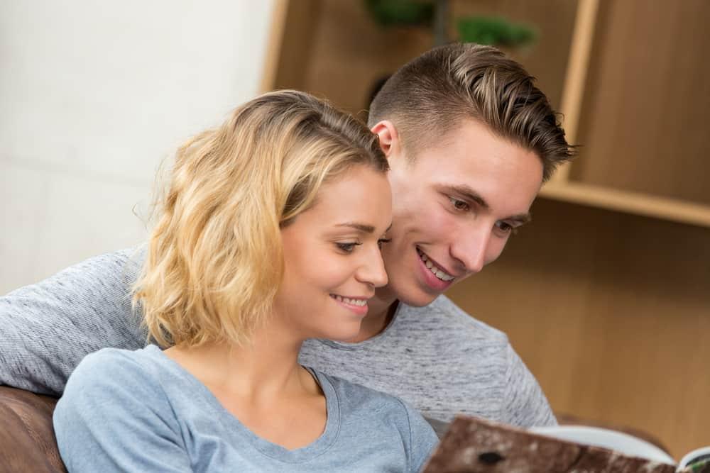 Eine Frau und ein Mann schauen sich etwas an und lachen