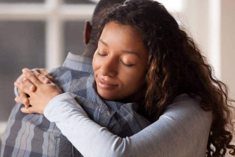 Glückliche gemischte Rassenfrau umarmen schwarzen Mann Ehemann