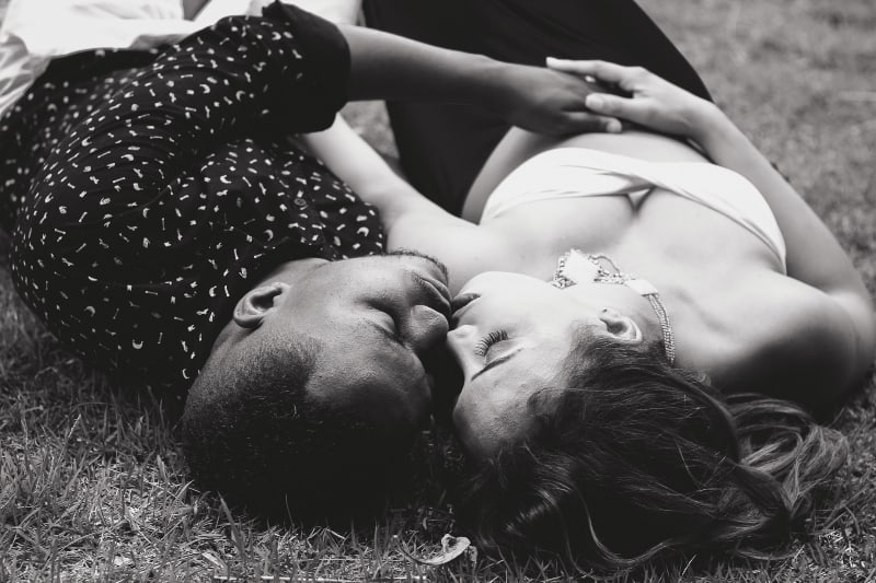 Graustufenfoto von Mann und Frau, die einander gegenüberstehen und auf Gras liegen