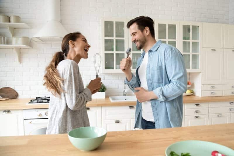 Lustiges junges Paar, das in Küchengeschirrmikrofonen in der Küche singt