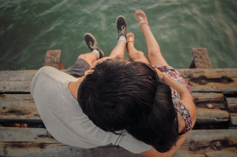 Mann und Frau umarmen sich auf braunem Holzdock