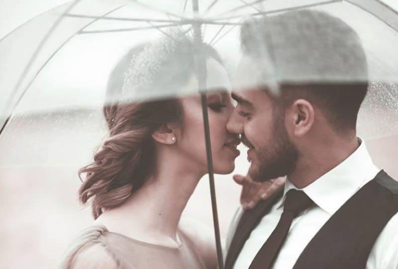 ein paar küssen sich unter einem regenschirm