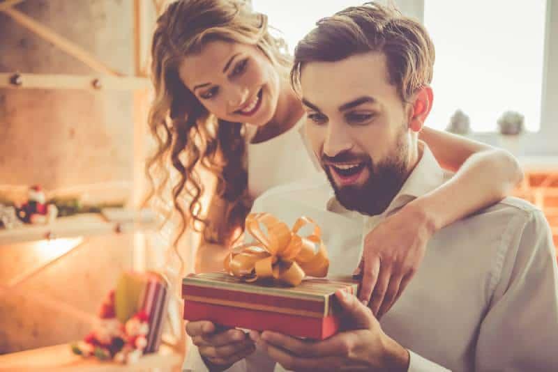Schönes junges Paar feiert zu Hause. Hübsches Mädchen gibt ihrem Freund eine Geschenkbox