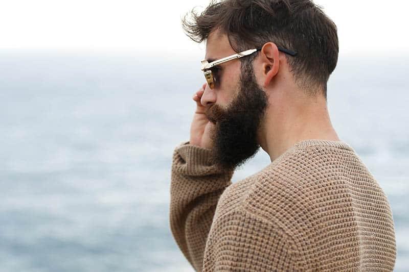 Seitenansicht des bärtigen Mannes, der Sonnenbrille und braunes Sweatshirt draußen trägt