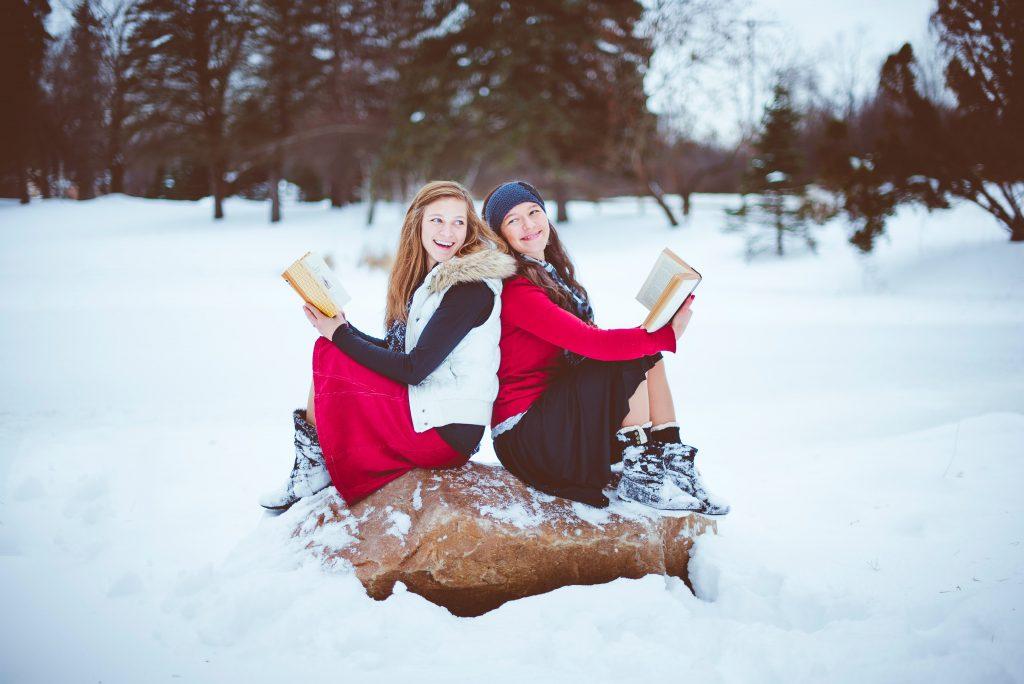 Zwei Frauen sitzen auf einem Felsen und lesen Bücher