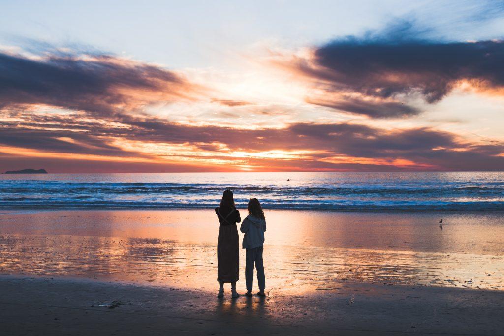 Zwei Mädchen an der Küste beobachten den Sonnenuntergang
