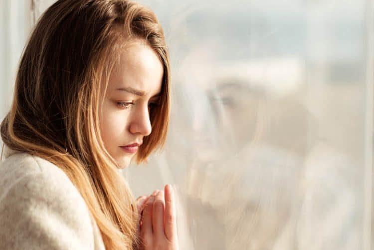 ein trauriges Mädchen, das sich gegen das Fenster lehnt