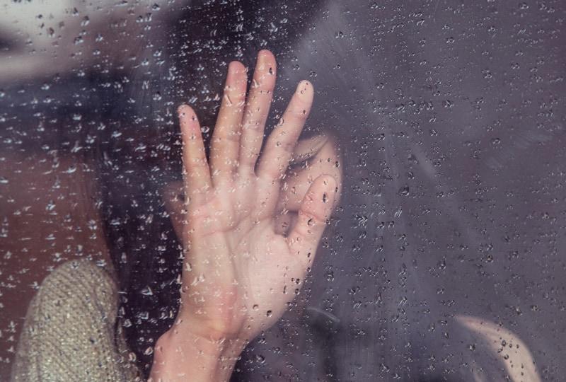 eine Frau berührt das Glas, auf dem es regnet