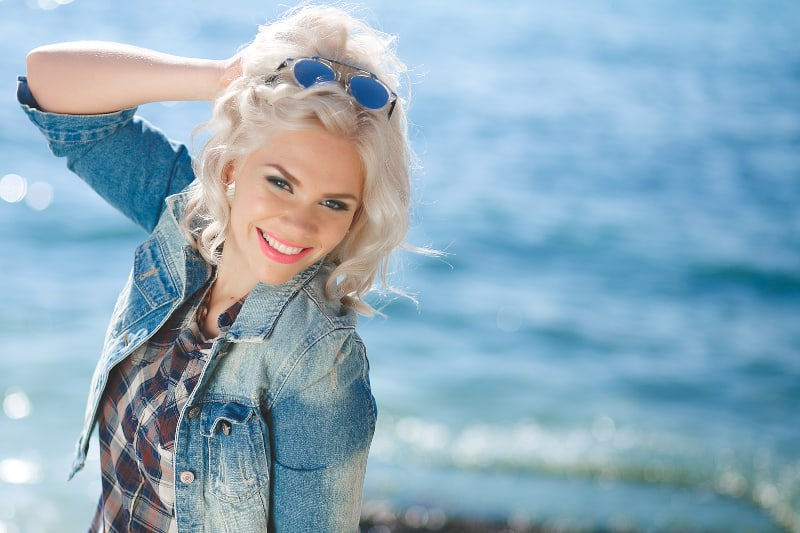 eine junge Blondine posiert am Meer