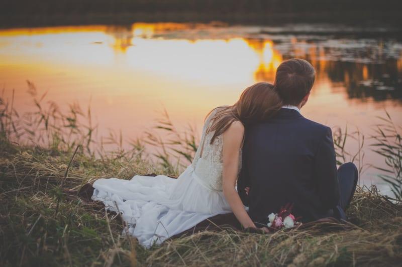 sitzende Frau, die sich während der goldenen Stunde auf die Schulter des Mannes mit Blick auf den See stützt