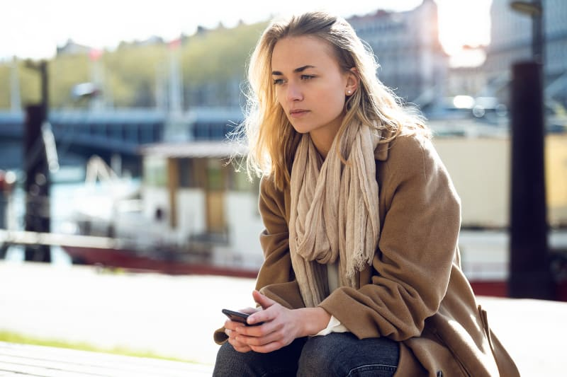 traurige Frau sitzt draußen traurig und denkt nach