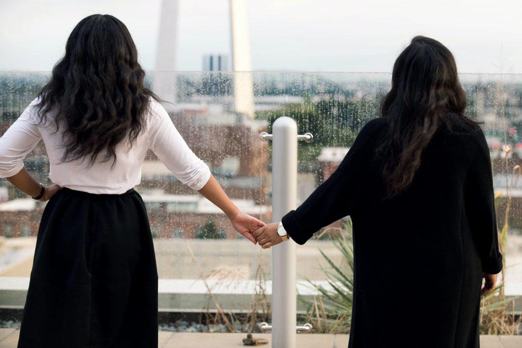 zwei schwarzhaarige Frauen Händchen haltend
