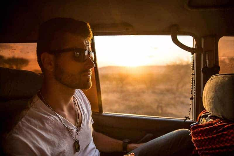 Mann trägt Sonnenbrille und fährt im Auto