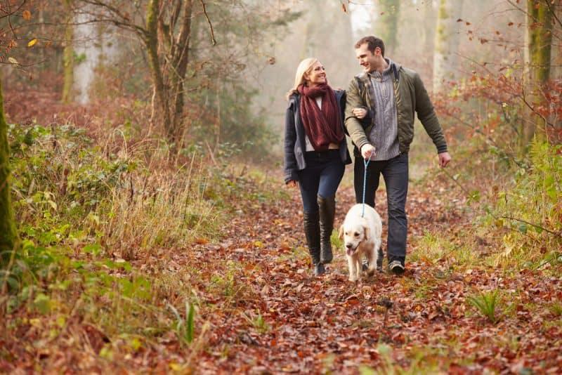 eine Frau mit einem Schal um den Hals und ein Mann, der mit einem Hund spazieren geht