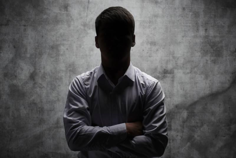 Anonymer Mann in einem Geschäftshemd mit verschränkten Armen vor einem dunklen Hintergrund