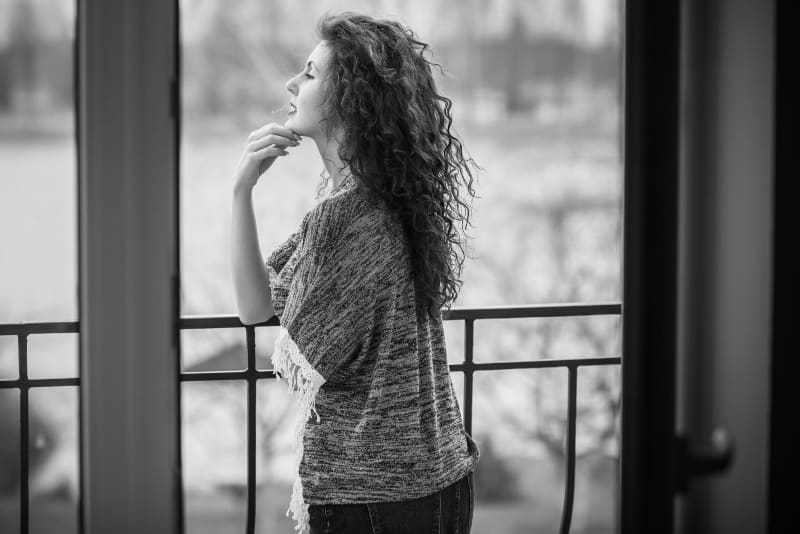 Auf dem Balkon steht eine junge Frau mit langen lockigen Haaren