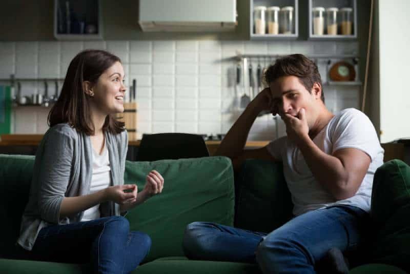 Der junge Mann gähnt und langweilt sich, als er der aufgeregten Frau zuhört, die spricht