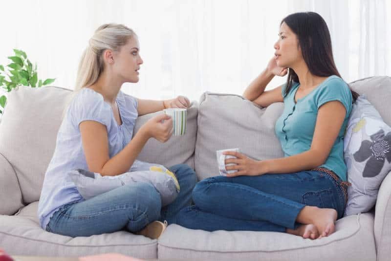 Freunde trinken Kaffee und unterhalten sich zu Hause ernsthaft auf der Couch
