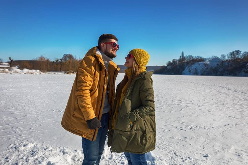 Draußen im Schnee steht ein liebevolles Paar und redet