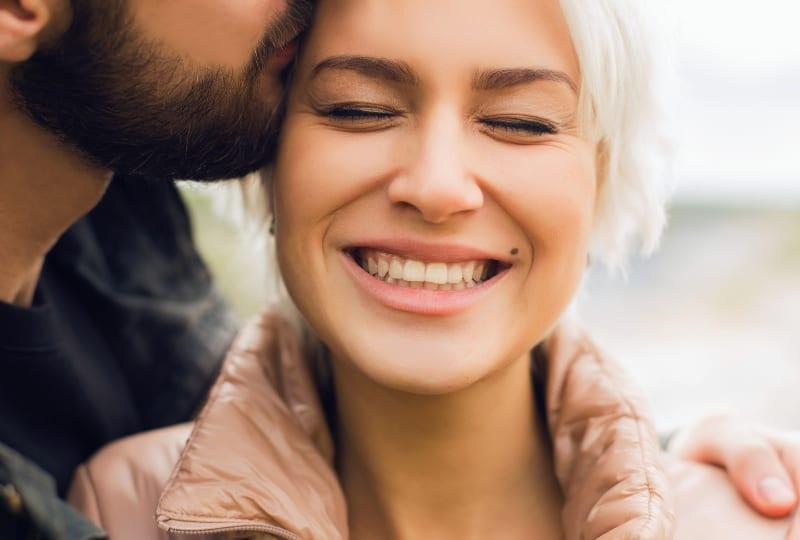 Ein Mann küsst ein Mädchen auf den Kopf