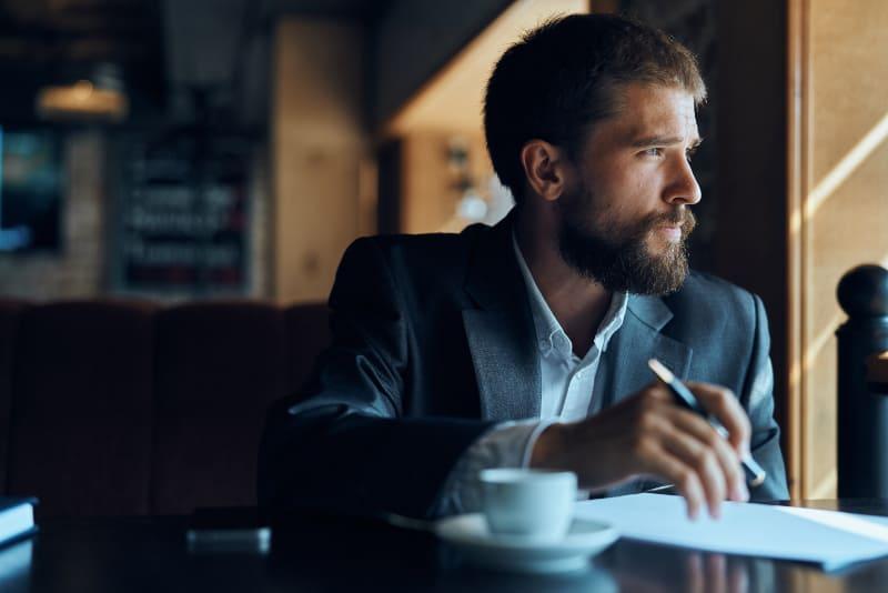 Ein Mann mit Bart schaut aus dem Fenster