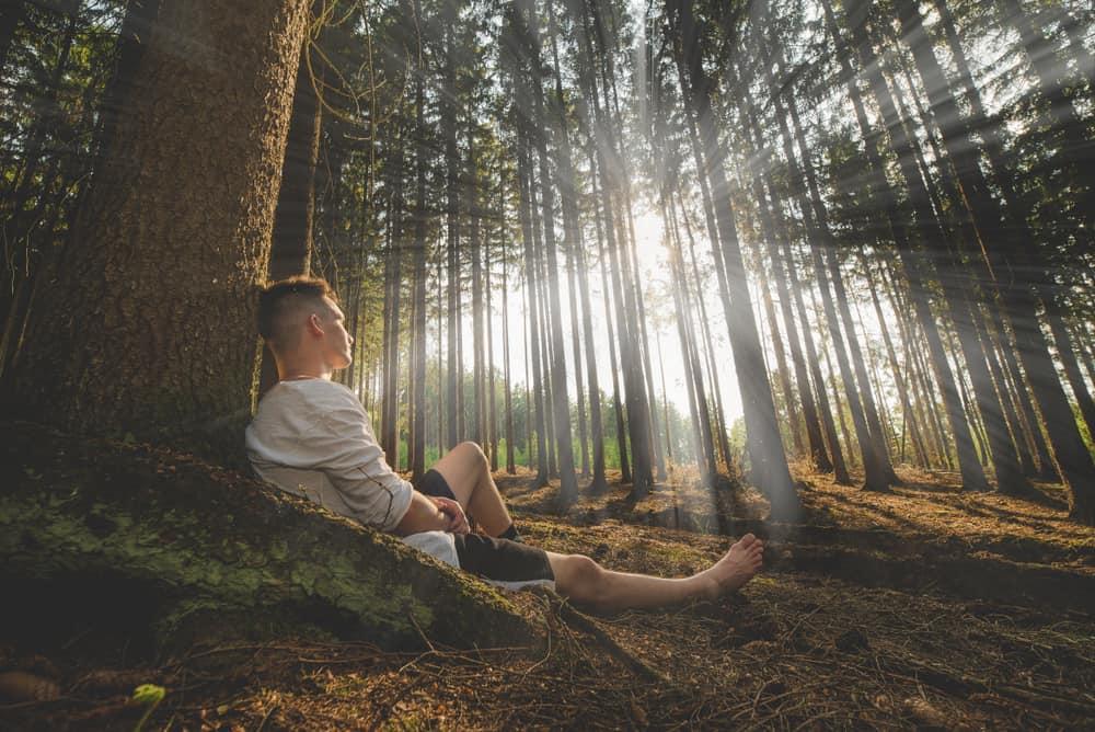 Ein Mann sitzt alleine im Wald
